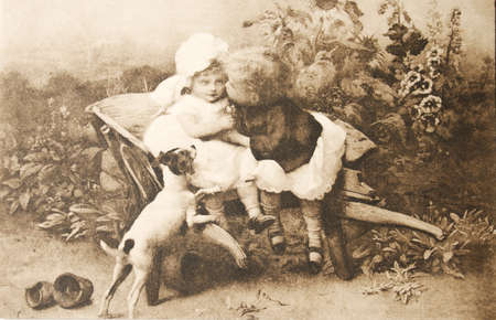 19th century: GERMANY-CIRCA 1902: Vintage postcard made of a photograph of two small children and a dog.  Elder boy kissing his sister. circa 1902