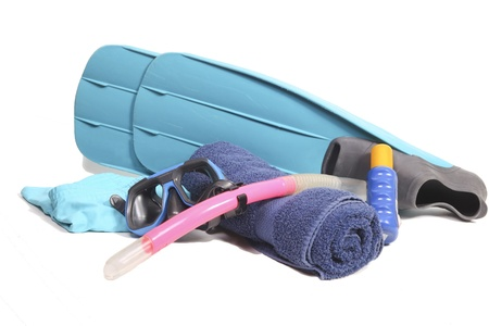 Flippers, snorkel, towel, suntan lotion and a swimsuit on white photo
