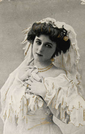 victorian valentine: FRANCE-CIRCA 1910:Postcard of beautiful young woman iin black and white and with golden color additions, circa 1910