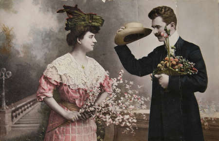 Vintage victorian handtinted photographic postcard of a young man and woman. Man lifts his head and offers flowers to the lady.