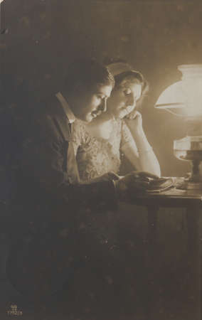 GREAT BRITAIN-CIRCA 1913: Loving couple reading a book together with oil lamp, circa 1913 in sepia