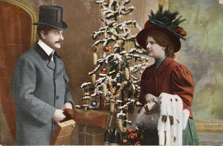 victorian valentine: vintage handtinted photographic postcard of around 1908 with a loving couple, packages and a tree. Editorial