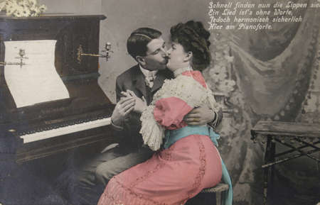 artifacts: German vintage postcard of 1909. Loving couple kissing at piano stool. With text  Circa 1909 print has many scratches, artifacts, fading, and solarization qualities.