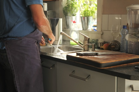 washing dishes in the kitchen with sunlight on water photo
