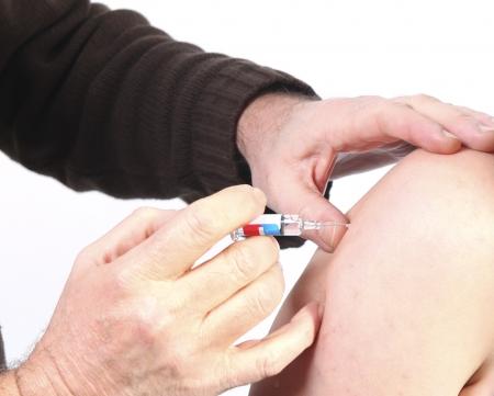 ワクチン接種: 若い女性の腕に予防接種を与える医者