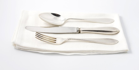 Silver spoon, knife and fork on white linen napkin photo