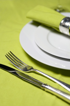 fine dining: table setting with plates, napkin, silverware and glass on apple green table cloth