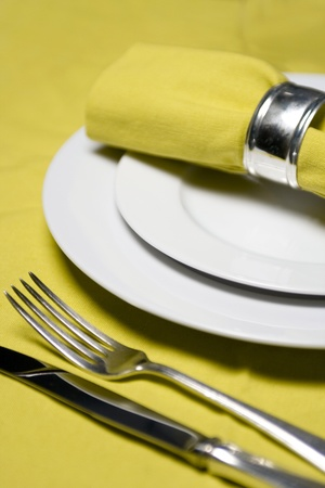 dining table and chairs: table setting with napkin, silverware and plates on yellow tablecloth