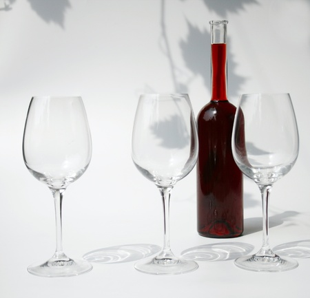 three empty wine glasses and a bottle filled with red wine against a background with the shadows of vine leaves photo
