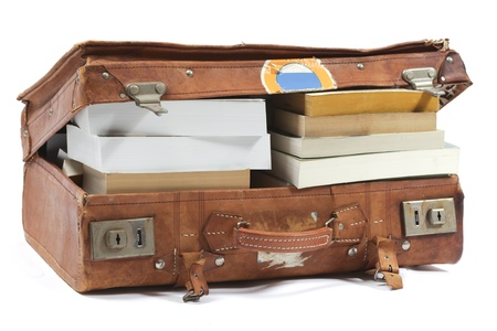 Leather suitcase filled with books photo