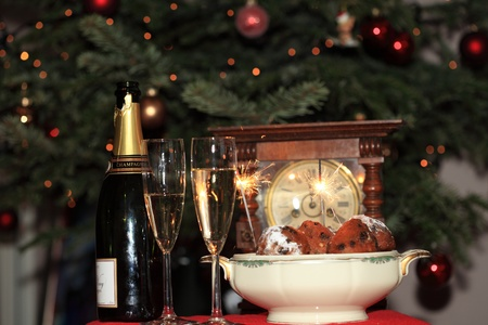 Champagne, Dutch oliebollen a clock and sparkles for new years eve. photo