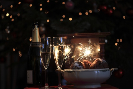 Champagne, Dutch oliebollen a clock and sparkles for new years eve. Stock Photo