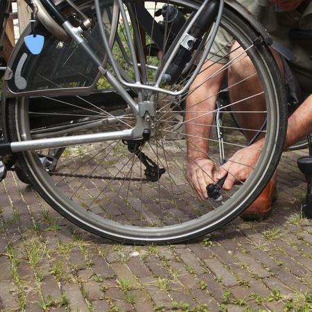 compresor: El hombre utiliza una válvula para inflar aire de las ruedas de la bicicleta Foto de archivo