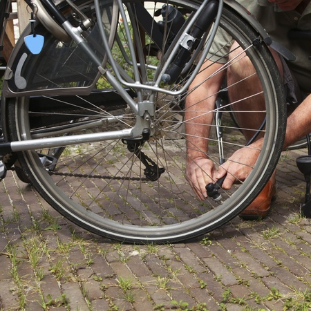 compressor: Man using valve for inflating air in tire of bike Stock Photo