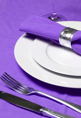 serviette: mesa con servilletas, cubiertos, platos y copa de vino sobre un mantel de color púrpura Foto de archivo