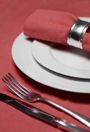 table setting with plates, napkin, silverware in a bright red color photo