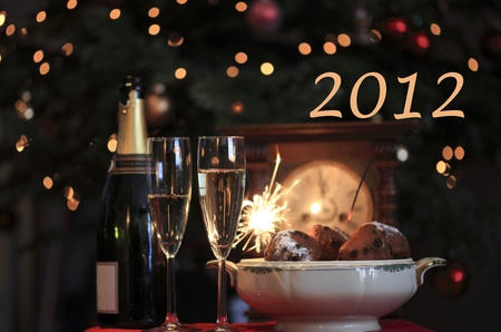 Happy new year 2012! New year design of a typical new Year's eve in the netherlands with champagne, sparkles and oliebollen Stock Photo - 10447357