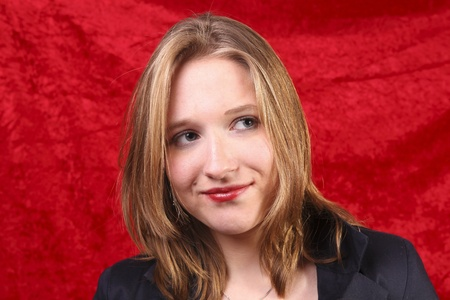 Close up  of a beautiful young girl in front of  a red velvet backdrop photo