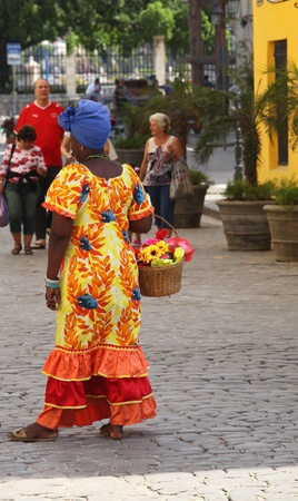 HAVANA-FEBRUARY 21: Young Woman with typical clothes and accessories on February 21,2011 in Havana. People dress in a way that represents the cuban nationality can be found in the streets of Old Havana posing for pictures by tourists
