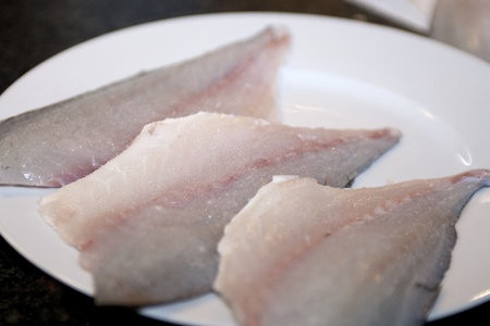 dorade: Three fresh seabass fillets on a plate Stock Photo