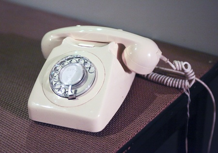 White rotating dial telephone from the seventies in retro style photo