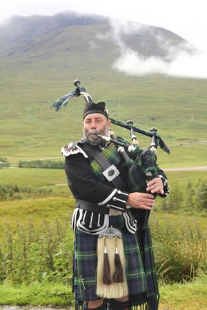 SCOTLAND-JULY, 16TH: Scotsman playing bagpipes on the road in the Highlands on July 16,2011