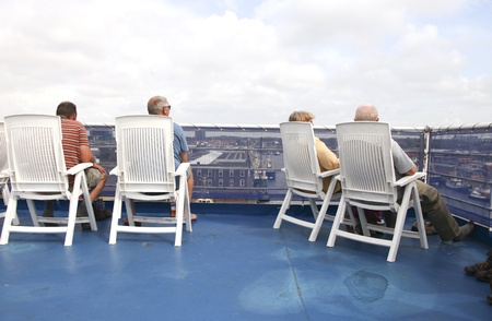 THE NETHERLANDS-JULY 10: People on the sundeck of cruise liner enjoying the view of IJmuiden in the Netherlands on july 10, 2011 Stock Photo - 10544101