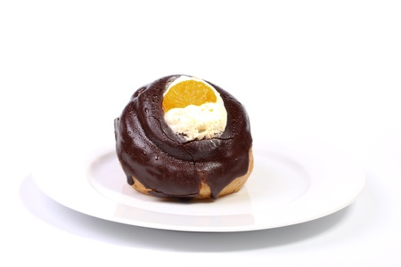profiterole: Chocolate covered profiterole with whipped cream on a plate