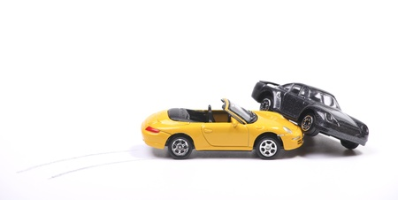 smash: Car crash between a yellow sportscar and a black sedan with brake tracks. Simulation with model cars Stock Photo