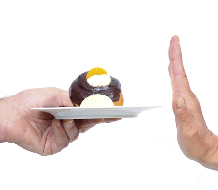 Female hand refuses unhealthy cake with whipped cream and chocolate