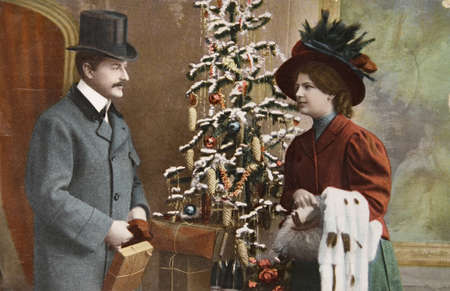 GERMANY- CIRCA 1915: Vintage christmas card printed in Germany in 1915 with loving couple beside a christmas tree  with presents, circa 1915.  Editorial