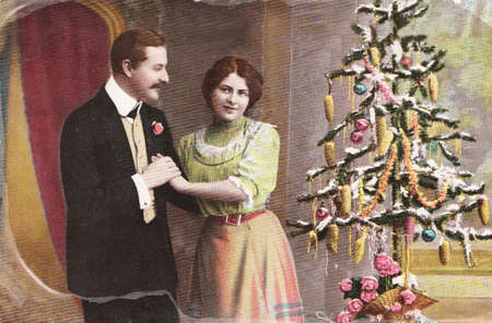 christmas costume: GERMANY- CIRCA 1910: Vintage christmas card printed in Germany in 1915 with loving couple beside a christmas tree  , circa 1910.