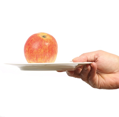 Hand offering an apple on a plate photo