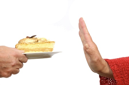 Hand gesturing stop to a cake on a plate
