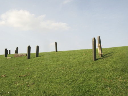 dikes: Graves on the dike of the sunken village of Oterdum. Oterdum is a Dutch village wich flooded because of the building of new dikes. The old graves have been restored on the new dike. Stock Photo