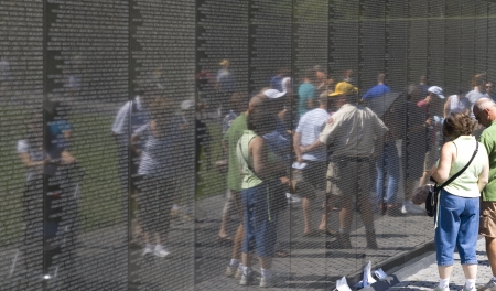 WASH DC - CIRCA SEPTEMBER 01: People looking at the names of Vietnam war casualties on Vietnam War Veterans Memorial circa september 01, 2008 in Washington DC, USA. Names in chronological order,from first casualty in 1959 to last in 1975.