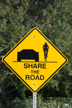 Yellow sign with text: share the road. Give bicycles more space