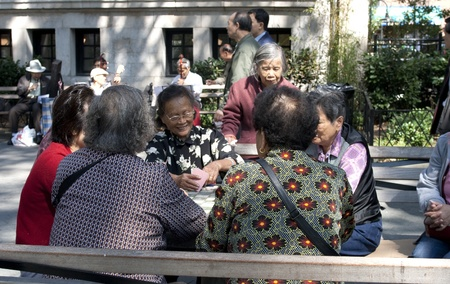 NYC, USA-SEPT 24: Chinese women in New York City Chinatown playing cards in the sun on sept 24, 2008. The cardgame is invented in China in the 9th century.