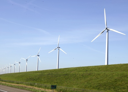 Windturbines on a dike in the Nertherlands near a motorway photo