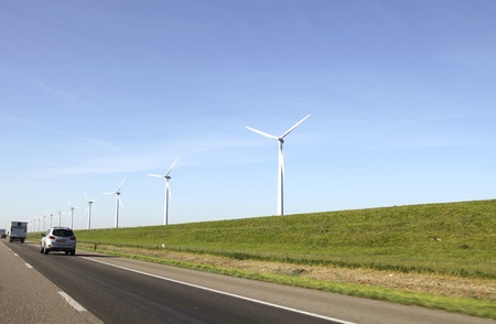 Windturbines on a dike near a motorway  with cars in the Netherlands Stock Photo - 10952212