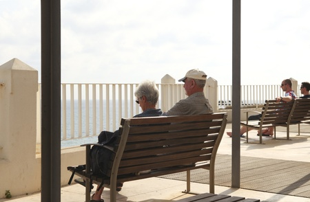 ALBUFEIRA, PORTUGAL-OCT 22:Senior couple relaxing and looking at ocean in south Portugal on oct 22, 2011. Many seniors from north Europe move to the south in winter to escape the cold climate.