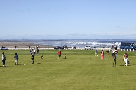 andrews: ST ANDREWS, UK-JULY 22: People putting on putting course at St. Andrews in Scotland on oct 22,2011. The old and famous golflinks of St.Andrews are beautifully situated with a view on beach and ocean