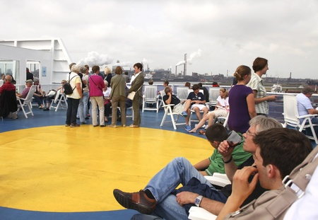 seaway: IJMUIDEN, THE NETHERLANDS- JULY 10: People on the sundeck of DFDS Seaway ferry between the Netherlands and Newcastle, England waiting for departure on Jul 10, 2011. DFDS offers daily departures from IJmuiden to Newcastle and vv and transports over 550.000