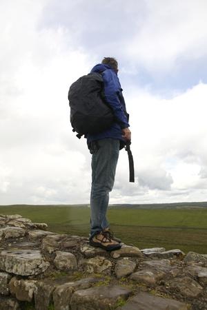 hadrian: Caminante de la muralla de Adriano en la lluvia admirando la vista Foto de archivo