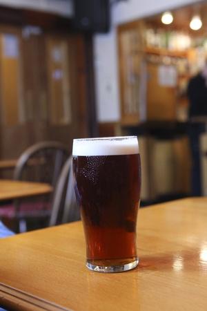 cerveza negra: Una pinta de cerveza oscura en una mesa de bar
