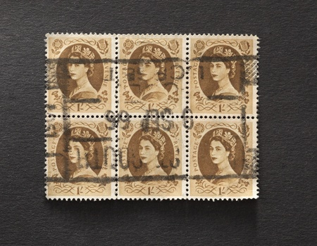 stamp collecting: UNITED KINGDOM - CIRCA 1952 to 1965: Six English One Shilling Brown Used Postage Stamps on a block  showing Portrait of Queen Elizabeth 2nd, circa 1952 to 1965  Editorial