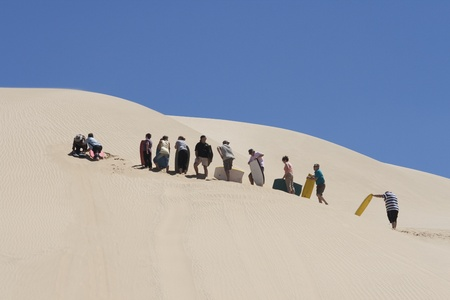 NEW ZEALAND-FEB 8: People waiting in line for the moment they can board downhill from a huge sand dune at 90 mile beach in New Zealand on Feb 8, 2009. This activity is offered in summer for tourists visiting 90 mile beach in NZ.