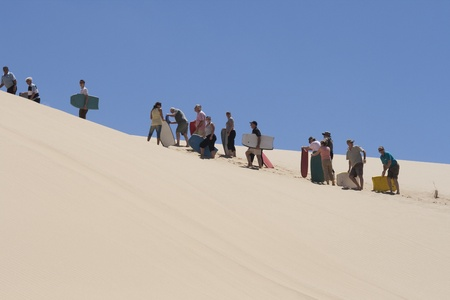 waiting in line: NEW ZEALAND-FEB 8: People waiting in line for the moment they can board downhill from a huge sand dune at 90 mile beach in New Zealand on Feb 8, 2009. This activity is offered in summer for tourists visiting 90 mile beach in NZ.