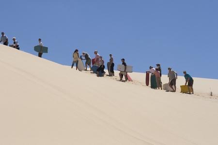 file d attente: NOUVELLE-ZÉLANDE-FEB 8: Les gens attendent en ligne pour le moment, ils peuvent monter à bord en aval d'un énorme dune de sable à 90 mile beach en Nouvelle-Zélande le 8 février 2009. Cette activité est offerte en été pour les touristes visitant la plage 90 mile en Nouvelle-Zélande.