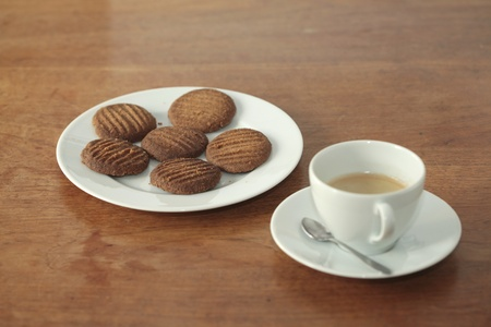 Homemade cookies on a plate with a cup of coffee on a wooden table photo